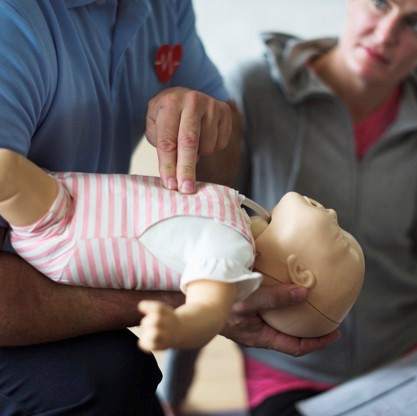 man giving CPR to baby